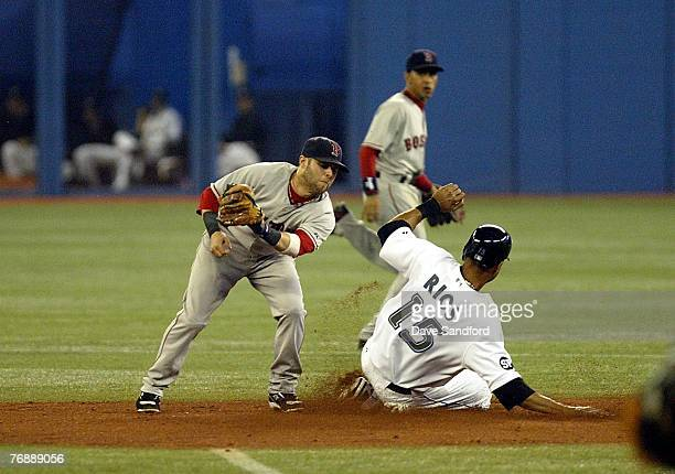 Alex Rios of the Toronto Blue Jays slides safely into 2nd base as Dustin Pedroia of the Boston Red Sox makes a late tag during their MLB game at the...