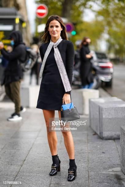 Alex Riviere wears a black dress, a silver scarf, a bag, Vuitton shoes, outside Louis Vuitton, during Paris Fashion Week - Womenswear Spring Summer...