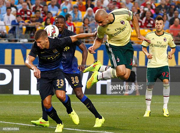 Alex Rodrigo Dias da Costa of AC Milan heads a ball in the first half against Matija NastasiÄ of Manchester City during International Champions Cup...