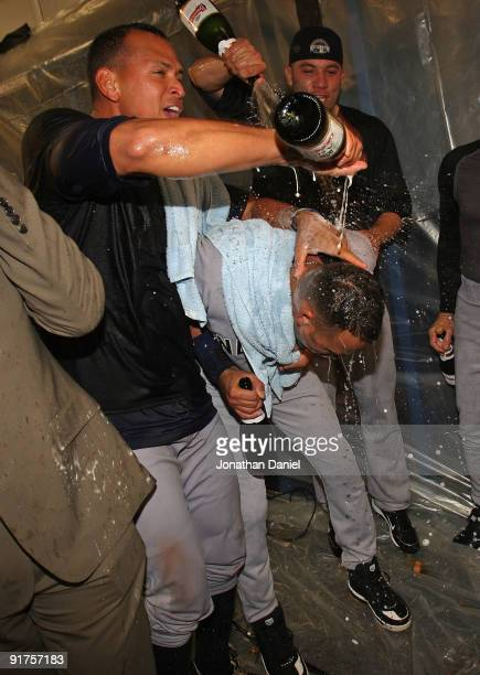 Alex Rodriguez and Alfredo Aceves of the New York Yankees douse teammate Derek Jeter with champagne after a win over the Minnesota Twins in Game...