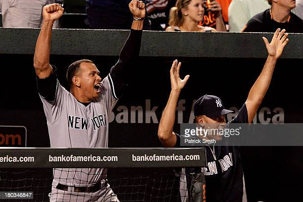 Alex Rodriguez and Derek Jeter of the New York Yankees celebrate as teammate Robinson Cano hits a home run against the Baltimore Orioles in the ninth...