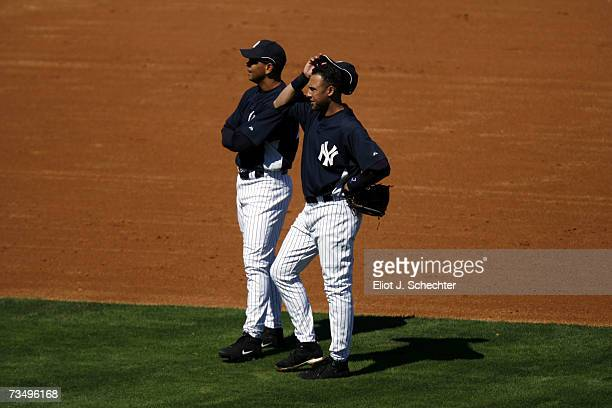 Alex Rodriguez and Derek Jeter of the New York Yankees take a break between pitches against the Detroit Tigers during a spring training game March 5...