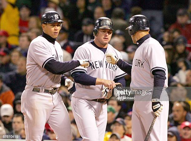 Alex Rodriguez and Jason Giambi of the New York Yankees are greeted at home by teammate Miguel Cairo after the two scored on a base hit by Robinson...