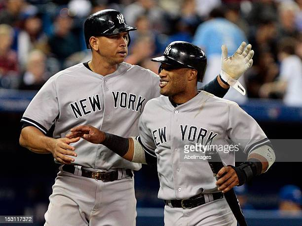 Alex Rodriguez and Robinson Cano of the New York Yankees celebrate a run against the New York Yankees during MLB action at the Rogers Centre...