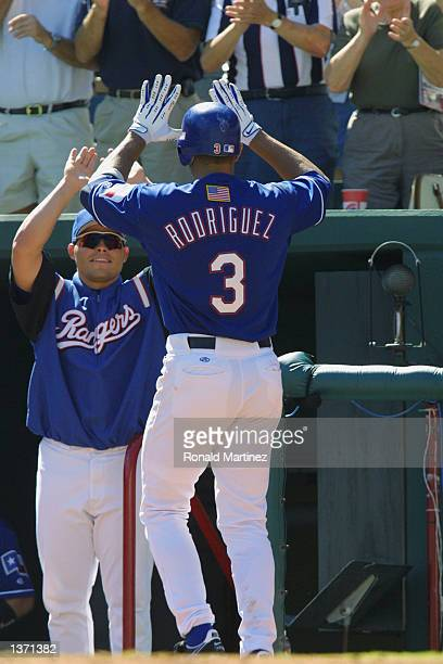 Alex Rodriguez is congratulated by Ivan Rodriguez of the Texas Rangers after a tworun homer against the Seattle Mariners on September 26 2001 at The...