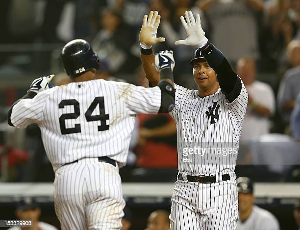 Alex Rodriguez of the New York Yankees and Robinson Cano celebrate after Cano hit a two run homer against the Boston Red Sox on October 3 2012 at...