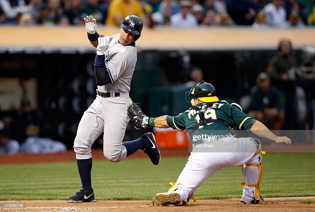 Alex Rodriguez #13 of the New York Yankees avoids being tagged by Josh Phegley #19 of the Oakland Athletics in the fourth inning at O.co Coliseum on May 28, 2015 in Oakland, California.