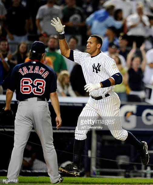 Alex Rodriguez of the New York Yankees celebrates a walk off home run in the 15th inning as losing pitcher Junichi Tazawa of the Boston Red Sox walks...