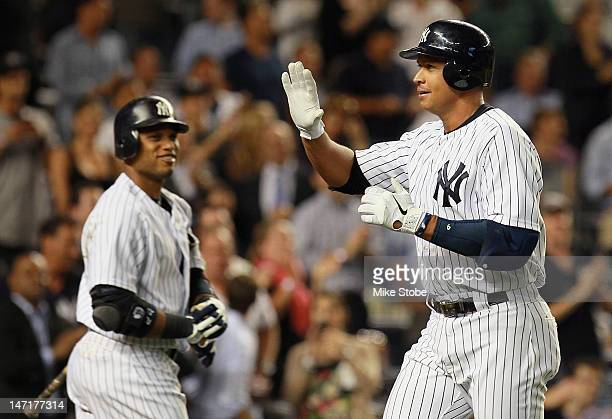 Alex Rodriguez of the New York Yankees celebrates after hitting a seventhinning homer as teammate Robinson Cano looks on during the game against the...