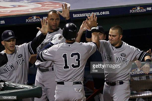 Alex Rodriguez of the New York Yankees celebrates after scoring in the eighth inning with manager Joe Girardi, Derek Jeter and Nick Swisher against...