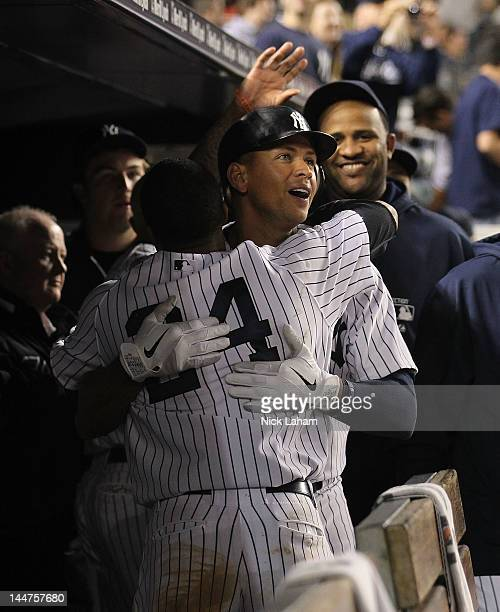 Alex Rodriguez of the New York Yankees celebrates with Robinson Cano in the dugout after a Raul Ibanez 2 RBI home run against the Cincinnati Reds at...