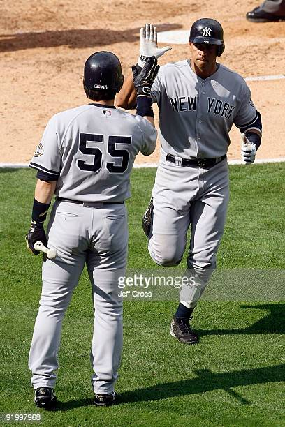 Alex Rodriguez of the New York Yankees celebrates with teammate Hideki Matsui after hitting a home run during the forth inning off Jered Weaver of...