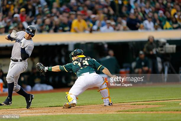 Alex Rodriguez of the New York Yankees eludes the tag by Josh Phegley of the Oakland Athletics to score a run during the game at Oco Coliseum on May...