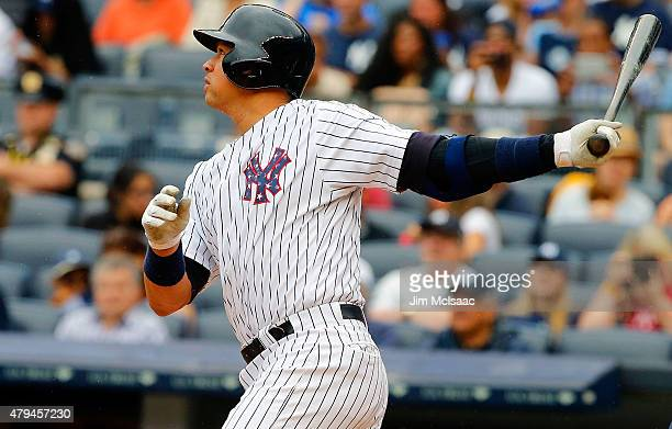 Alex Rodriguez of the New York Yankees follows through on a first inning RBI base hit against the Tampa Bay Rays at Yankee Stadium on July 4 2015 in...