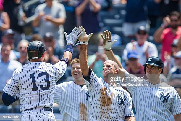 Alex Rodriguez of the New York Yankees high fives team mates Chase Headley Brett Gardner and Mark Teixeira after hitting a home run during the game...