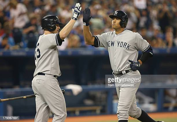 Alex Rodriguez of the New York Yankees is congratulated by Lyle Overbay after hitting a solo home run in the fifth inning during MLB game action...