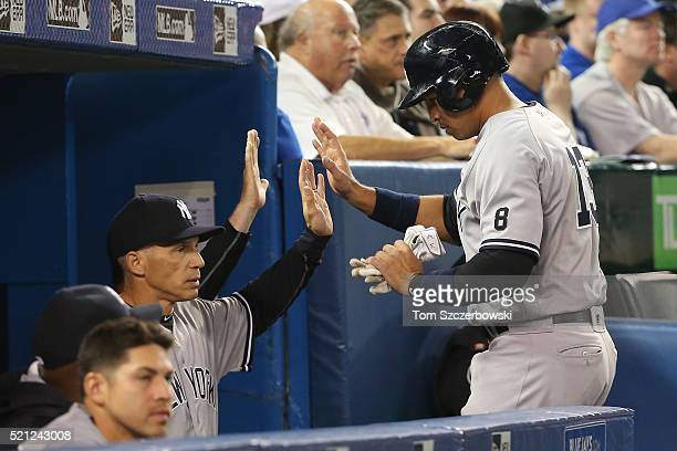 Alex Rodriguez of the New York Yankees is congratulated by manager Joe Girardi after scoring a run in the fourth inning during MLB game action...