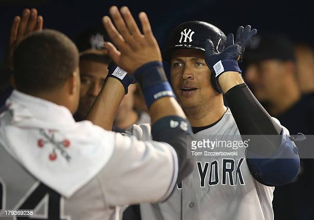 Alex Rodriguez of the New York Yankees is congratulated by Robinson Cano after hitting a solo home run in the fifth inning during MLB game action...