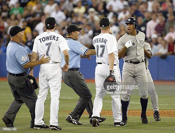 Alex Rodriguez of the New York Yankees is held back by firstbase coach Tony Pena as he has some words with Lyle Overbay and pitcher Josh Towers of...