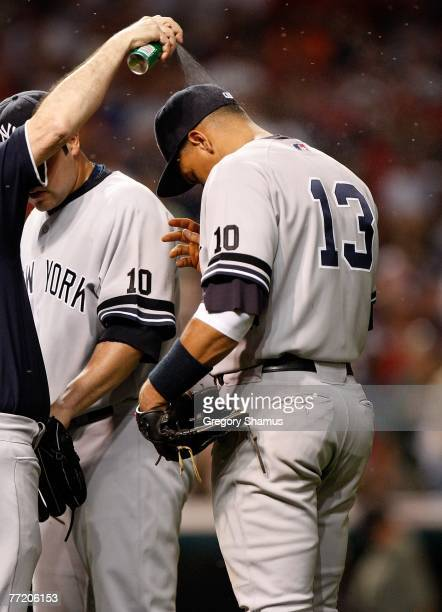 Alex Rodriguez of the New York Yankees is sprayed with bug spray to combat the swarms of gnats which covered the field against the Cleveland Indians...