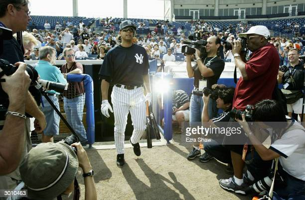 Alex Rodriguez of the New York Yankees is surrounded by media as he walks onto the field to take batting practice at the Yankees spring training...