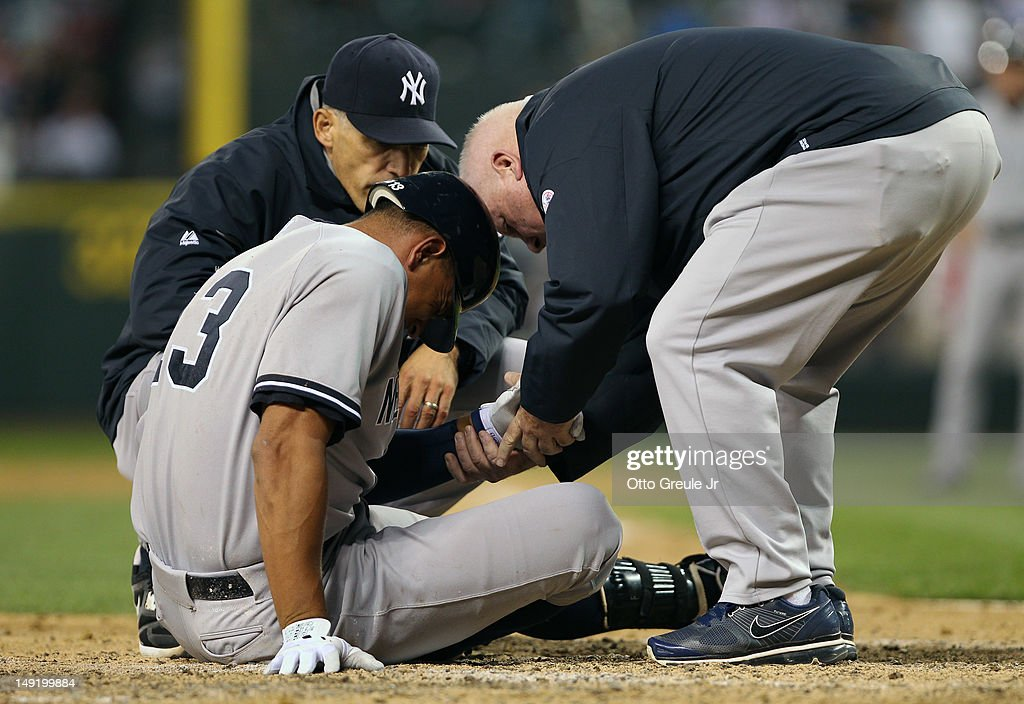 Alex Rodriguez #13 of the New York Yankees is tended to by manager Joe Girardi #28 (L) and a trainer after being hit with a pitch on the arm by starting pitcher Felix Hernandez of the Seattle Mariners at Safeco Field on July 24, 2012 in Seattle, Washington. Rodriguez was removed from the game.