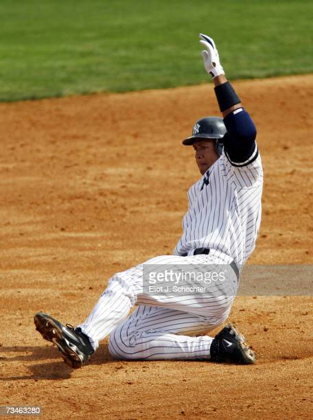 Alex Rodriguez of the New York Yankees is unsuccessful sliding into third base safely against the Minnesota Twins during a Spring Training game on...