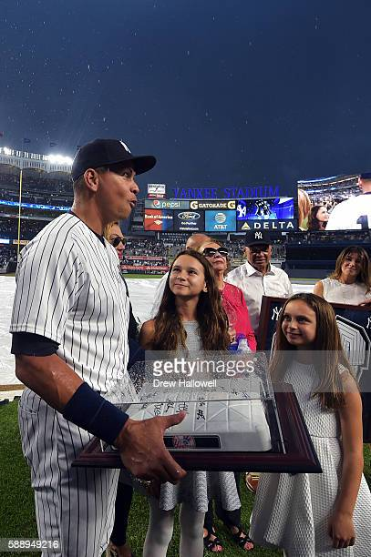 Alex Rodriguez of the New York Yankees reacts as he stands with his daughters Natasha and Ella after being presented with an autographed base by the...