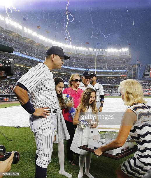 Alex Rodriguez of the New York Yankees receives commemorative gifts in a thunderstorm during a pregame ceremony for his retirement at Yankee Stadium...