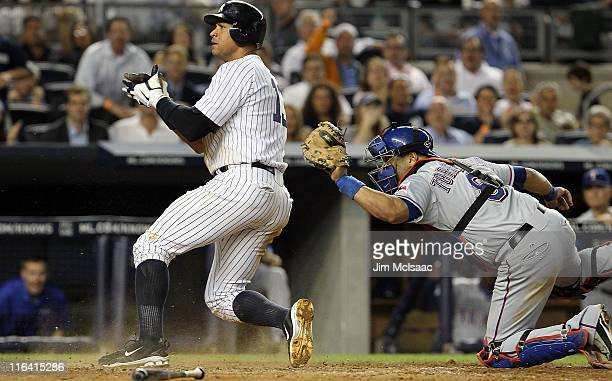 Alex Rodriguez of the New York Yankees scores a fifth inning run ahead of the tag from Yorvit Torrealba of the Texas Rangers on June 15, 2011 at...