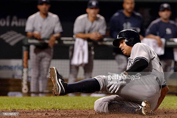 Alex Rodriguez of the New York Yankees scores off of a hit by Robinson Cano of the New York Yankees against the Baltimore Orioles in the eighth...