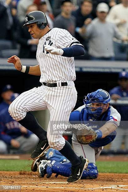 Alex Rodriguez of the New York Yankees scores past the tag attempt of catcher Matt Treanor of the Texas Rangers in the bottom of the second inning of...