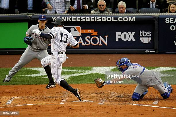 Alex Rodriguez of the New York Yankees scores past the tag attempt of catcher Matt Treanor of the Texas Rangers as CJ Wilson backs him up in the...