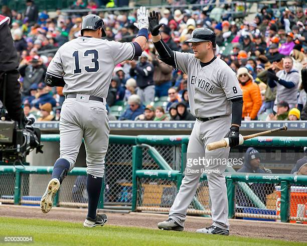 Alex Rodriguez of the New York Yankees slaps hands with teammate Brian McCann of the New York Yankees after hitting a home run in the first inning...