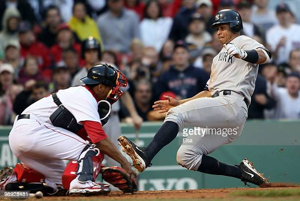 Alex Rodriguez of the New York Yankees slides home safely as Victor Martinez of the Boston Red Sox is unable to make the tag on May 8, 2010 at Fenway...