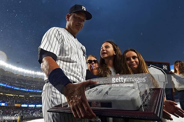 Alex Rodriguez of the New York Yankees stands with his daughters Natasha and Ella as he looks at an autographed base given to him by the team during...