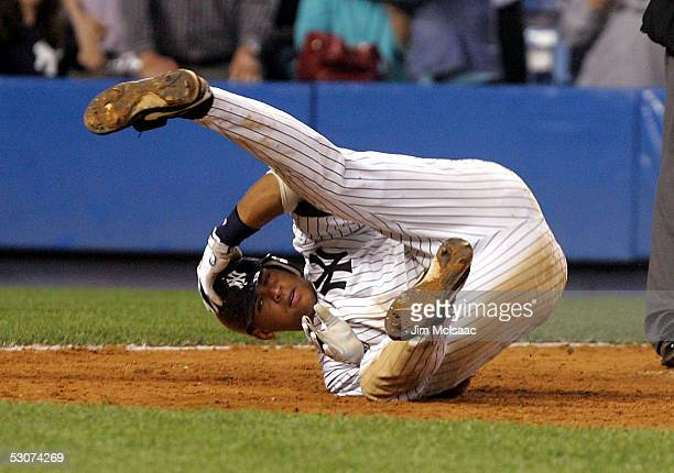 Alex Rodriguez of the New York Yankees tumbles to the ground after getting tagged out at home trying to score the winning run in the ninth inning...