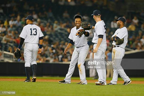Alex Rodriguez of the New York Yankees walks away as Robinson Cano Lyle Overbay and Eduardo Nunez laugh during the game against the Los Angeles...