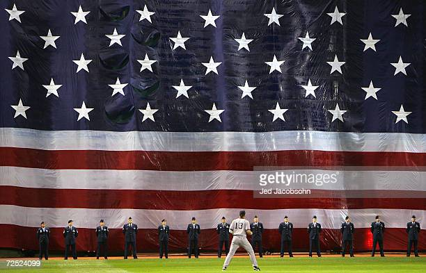 """Alex Rodriguez of the New York Yankees warms-up as an American flag is drapped in front of the """"Green Monster"""" for the singing of the National Anthem..."""