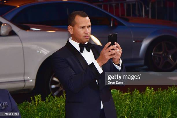 Alex Rodriguez taking a shot of Jennifer Lopez on the red carpet of the Rei Kawakubo/Comme des Garcons Art Of The InBetween Costume Institute Gala at...