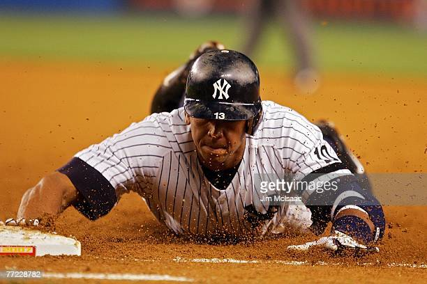 Alex Rodriguez#13 of the New York Yankees slides back into first in front of the tag against the Cleveland Indians during Game Three of the American...