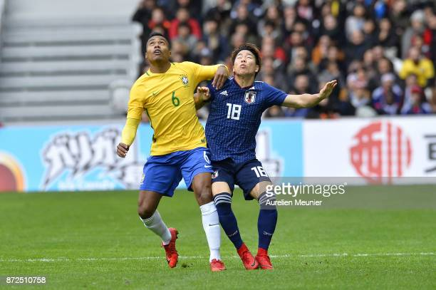 Alex Sandro of Brazil and Takuma Asano of Japan fight for the ball during the international friendly match between Brazil and Japan at Stade...