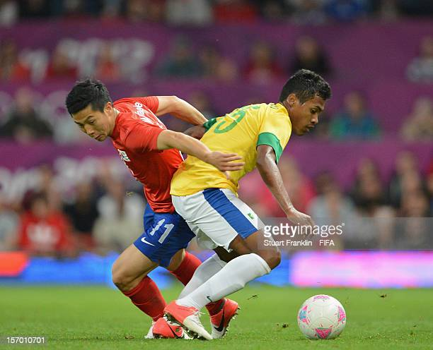 Alex Sandro of Brazil challenges for the ball with Jongwoo Park of Korea during the Olympic games 2012 mens semi final match between Korea and Brazil...
