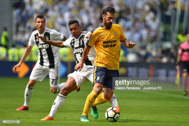 Alex Sandro of Juventus competes for the ball with Antonio Caracciolo of Hellas Verona FC during the serie A match between Juventus and Hellas Verona...