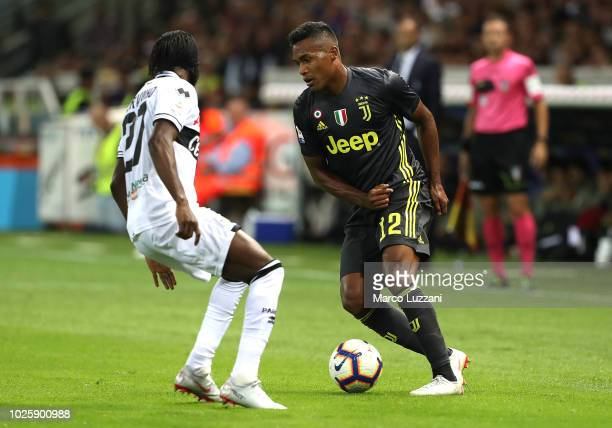 Alex Sandro of Juventus competes for the ball with Gervinho of Parma Calcio during the serie A match between Parma Calcio and Juventus at Stadio...