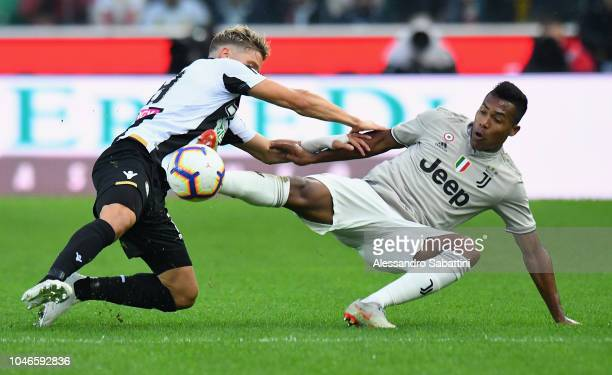 Alex Sandro of Juventus competes for the ball with Jens Stryger Larsen of Udinese Calcio during the Serie A match between Udinese and Juventus at...