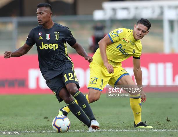 Alex Sandro of Juventus FC competes for the ball with Mariusz Stepinski of Chievo Verona during the Serie A match between Chievo Verona and Juventus...