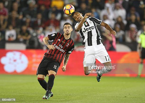 Alex Sandro of Juventus FC in action against Fernandez Suso of AC Milan during the Supercoppa TIM Doha 2016 match between Juventus FC and AC Milan at...