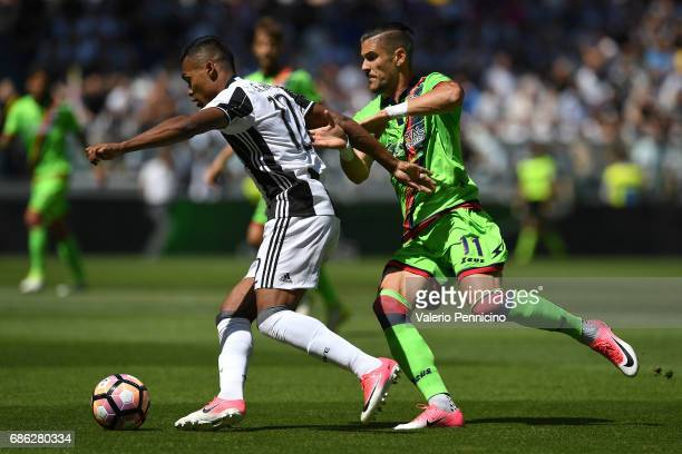 Alex Sandro of Juventus FC is challenged by Diego Falcinelli of FC Crotone during the Serie A match between Juventus FC and FC Crotone at Juventus...