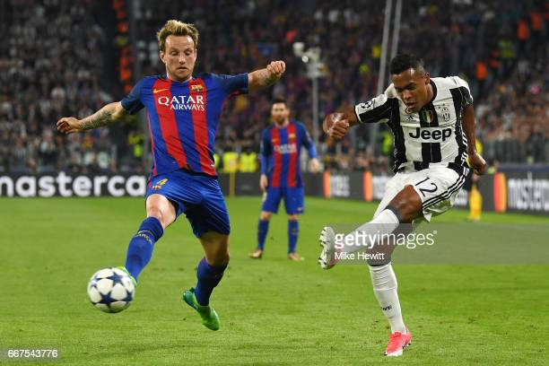 Alex Sandro of Juventus gets in a cross despite the efforts of Ivan Rakitic of Barcelona during the UEFA Champions League Quarter Final first leg...